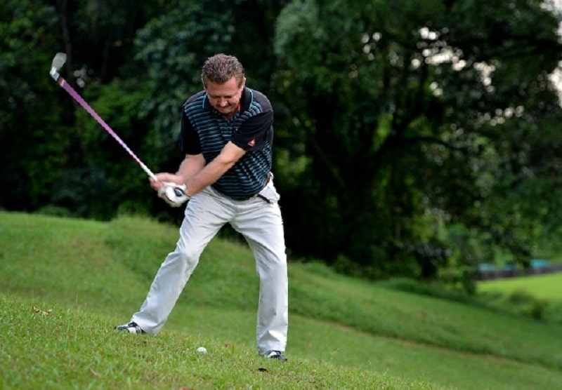 Trường hợp bóng golf nằm ở vị trí thấp hơn nền đất thì bạn nên đặt nó ở giữa tư thế đứng